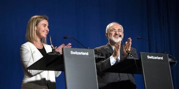 Iranian Foreign Minister Javad Zarif, right, claps with European Union High Representative for Foreign...