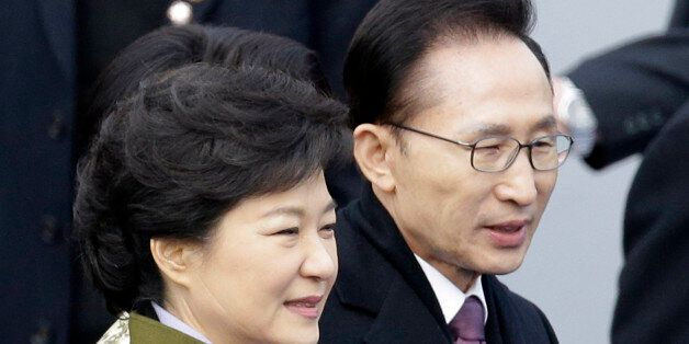 ADDS INFORMATION ON THE SCAR ON HER FACE - South Korea's new President Park Geun-hye, left, walks with...