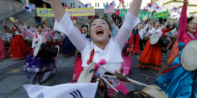 South Korean Christian women perform during a gathering to pray for the speedy recovery of U.S. Ambassador...