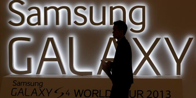 In this photo taken on April 25, 2013, a man walks by a logo of Samsung Electronics Co.'s latest smartphone...