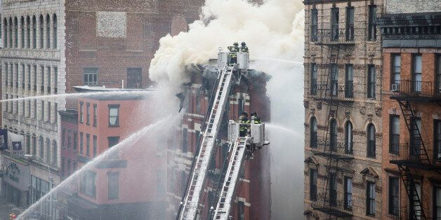 New York City firefighters work the scene of a large fire and a partial building collapse in the East...