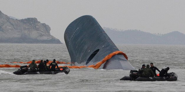 FILE - In this April 17, 2014 file photo, South Korean Coast Guard officers search for missing passengers...