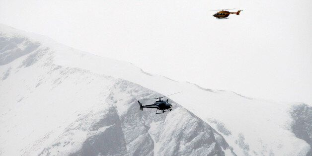 Rescue helicopters fly over the mountainside near Seyne-les-Alpes, French Alps, Tuesday, March 24, 2015....