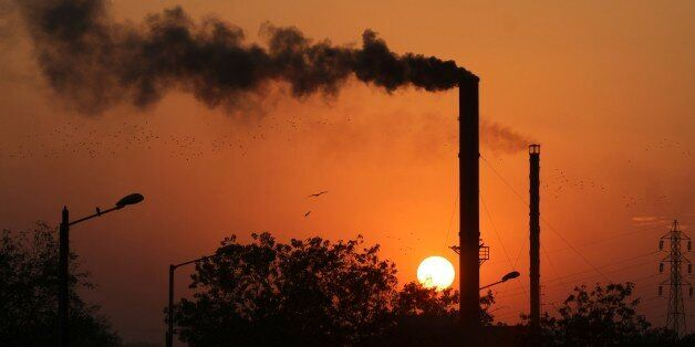 Birds fly past at sun set as smoke emits from a chimney at a factory in Ahmadabad, India, Monday, Dec....