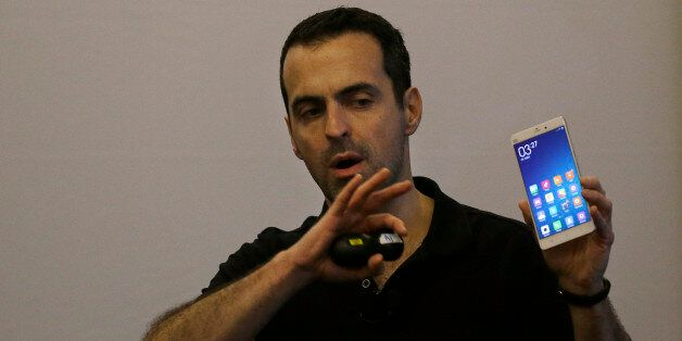 Xiaomi vice president of global operations Hugo Barra holds up a Mi Note during a presentation in San...