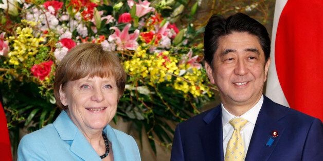 German Chancellor Angela Merkel and Japanese Prime Minister Shinzo Abe pose for photographers prior to...