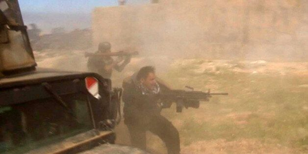 In this still image taken from video soldiers fire towards a target in Tikrit, Iraq on Wednesday, March...
