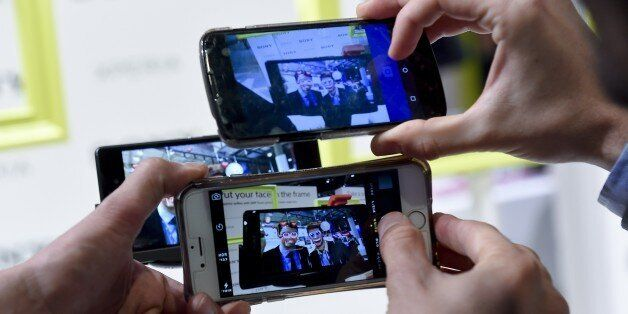 Visitors use their mobile phones' cameras during the 2015 Mobile World Congress (MWC) in Barcelona on...