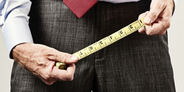Cropped shot of a man holding a tape measure over his pelvis, apparently checking to see whether his...