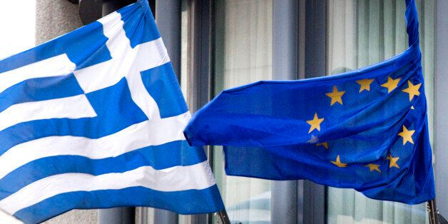 The Greek, left, and EU flag flap in the wind outside the Greek embassy in Brussels on Friday, Feb. 20,...