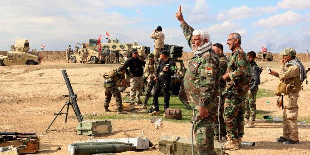In this Wednesday, March 4, 2015 photo, Iraqi army soldiers and volunteers prepare to launch mortar shells...