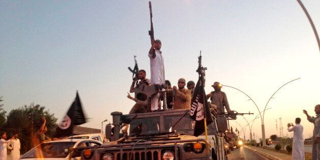 FILE - In this photo taken Monday, June 23, 2014, fighters from the Islamic State group parade in a commandeered...