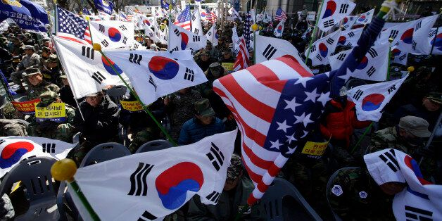 South Korean Vietnam War veterans hold flags from South Korea and the United States during a rally denouncing...