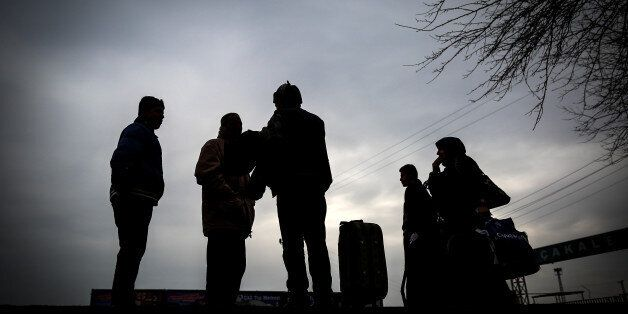 People are seen at the Akcakale border gate in Turkey, Saturday, Jan. 31, 2015, as some others wait for...