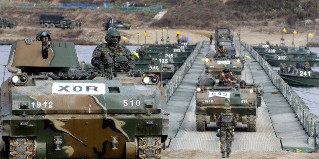 South Korean armored army vehicles cross a floating bridge on the Nam Han River during an annual military...