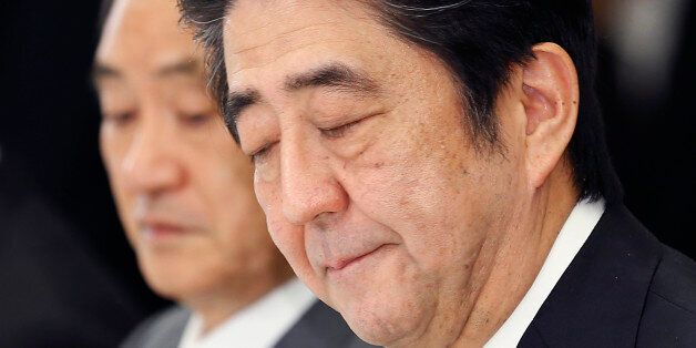 In this Wednesday, Feb. 25, 2015 photo, Japanese Prime Minister Shinzo Abe bites his lips during a meeting...
