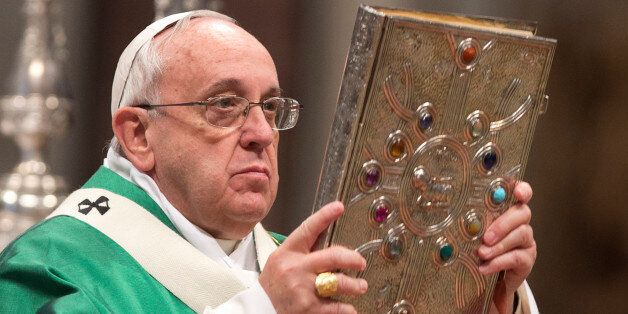 Pope Francis holds the Gospels book as he celebrates a Mass for newly-elected cardinals, in St. Peter's...