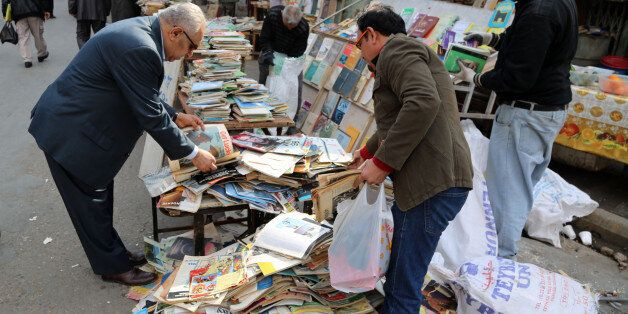 In this Friday, Jan. 23, 2015 photo, Iraqis look at books on al-Mutanabi Street, home to the city's book...