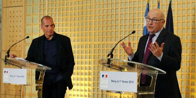 French Finance Minister Michel Sapin, right, addresses reporters during a joint press conference with...