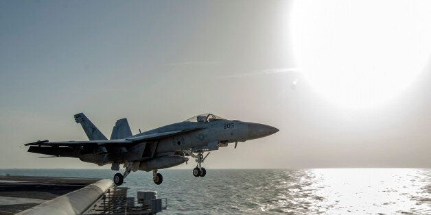 In this image released by the U.S. Navy on Friday, Dec. 5, 2014, a fighter jet launches from the flight...
