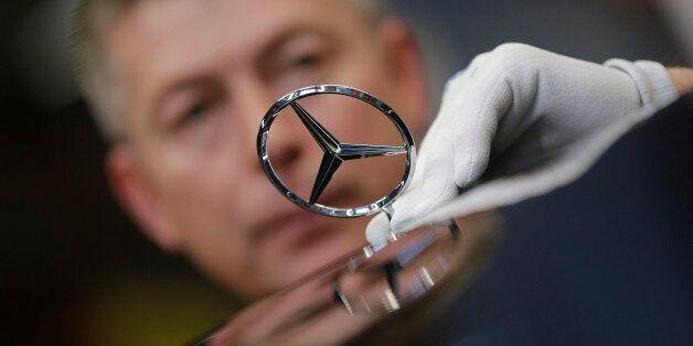 An employee fixes a car emblem as he assembles a Mercedes-Benz S-class model at the plant in Sindelfingen,...