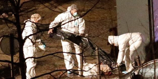 Police officers remove a body lying outside the kosher market, in Paris, Friday Jan. 9, 2015. What started...