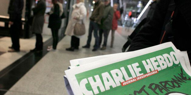 People queue up to buy the new issue of Charlie Hebdo newspaper at a newsstand in Paris Wednesday, Jan....