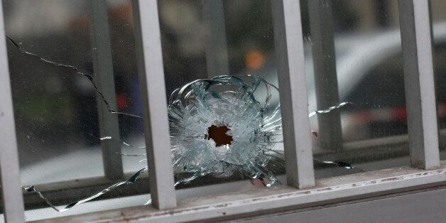 A bullet impact is seen in a window of a building next to the French satirical newspaper Charlie Hebdo's...