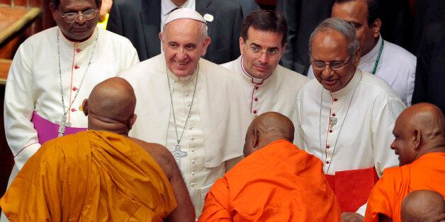 Pope Francis smiles as he speaks to Buddhist monks after an inter-religious meeting in Colombo, Sri Lanka,...