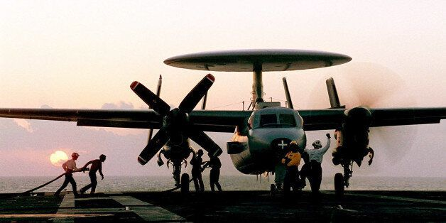 In this undated handout photo from the French Navy, technicians refuel a hawkeye plane on the flight...