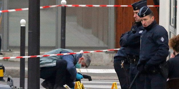 French investigating police officer takes photos outside the door of the French satirical newspaper Charlie...