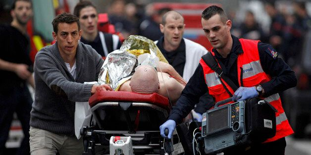 An injured person is evacuated outside the French satirical newspaper Charlie Hebdo's office, in Paris,...