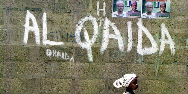 FILE - In this April 18, 2003, file photo a girl walks past a wall with graffiti about the al-Qaida network...