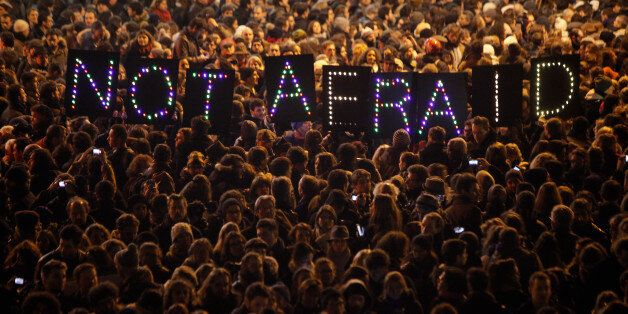 People gather in solidarity of the victims of a terror attack against a satirical newspaper, in Paris,...