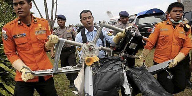 인도네시아 국가수색구조청 요원들이 5일(현지시간) 자바해에서 수거돼 미 해군 헬기편으로 팡카란분 공항에 도착한 에어아시아 8501기의 좌석 잔해들을 옮기고