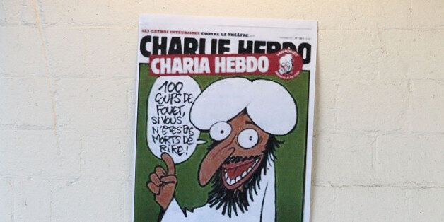 Publishing director of the satyric weekly Charlie Hebdo, Charb, displays the front page of the newspaper...