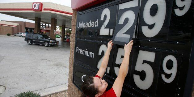 In this Friday, Dec. 12, 2014 photo, Quick Trip clerk Roxana Valverde adjusts the gas price sign numbers...