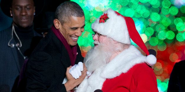President Barack Obama greets Santa on stage during the National Christmas Tree lighting ceremony at...