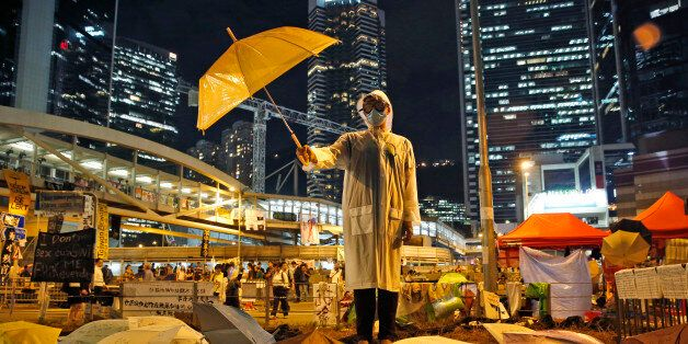 AP10ThingsToSee - A protester holds an umbrella during a performance on a main road in the occupied areas...
