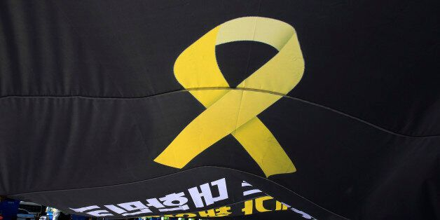 Workers carry a flag depicting a yellow ribbon as a sign of hope for the safe return of missing passengers...
