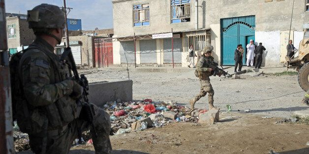 A U.S. soldier, left, takes his position at the site of a suicide attack in Kabul, Afghanistan, Monday,...