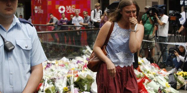 A woman cries after laying a flower at a makeshift memorial in Sydney, Australia Tuesday, Dec. 16, 2014...