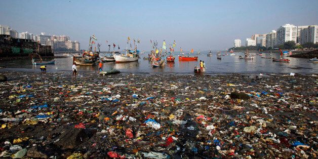 Indian men work near plastic and other waste at seashore near Colaba in Mumbai, India, Sunday, Nov. 4,...