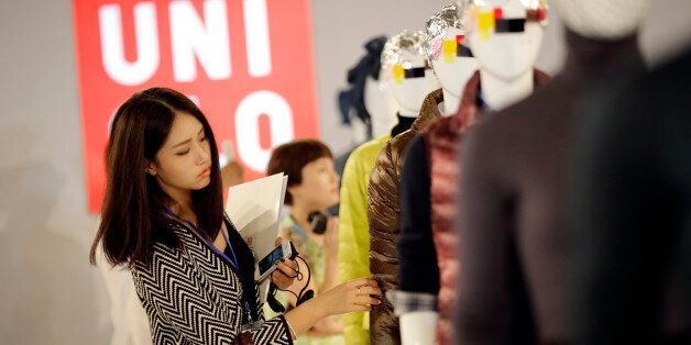 A journalist looks at the latest collection of Uniqlo brands during a press conference in Shanghai, China,...