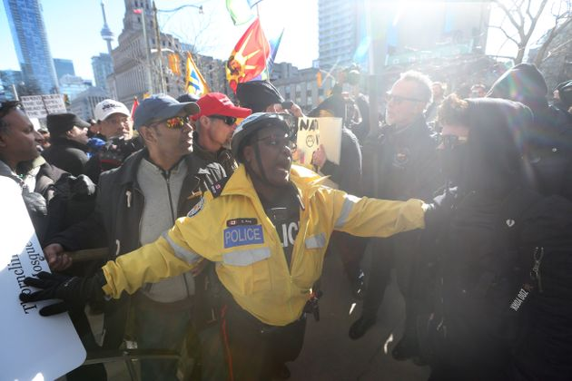 Police keep about 40 anti-Muslim protesters and several hundred counter protesters apart during a Toronto...