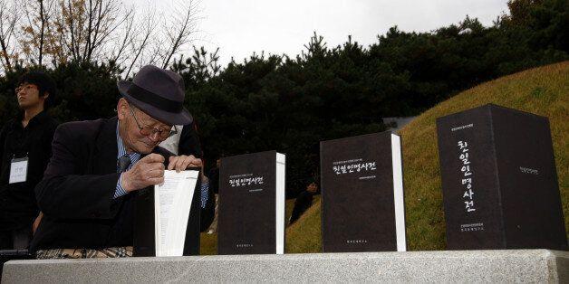 친일인명사전발간 국민보고대회가 서울 용산구 효창동 효창공원 백범 김구 묘역에서 8일 오후 한 참가자가 백범 김구 묘역에 바쳐진 친일인명사전을 보고