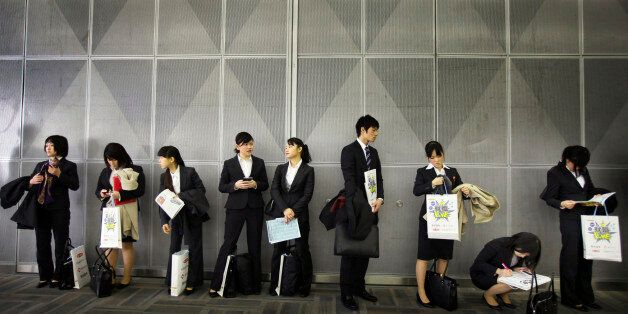A group of graduates waits in queue before attending a company's briefing session as they look for a...