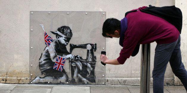 한 남자가 런던에서 뱅크시의 그래피티를 찍고