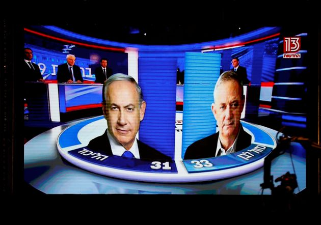The results of the exit polls are shown on a screen at Benny Gantz's Blue and White party headquarters,...