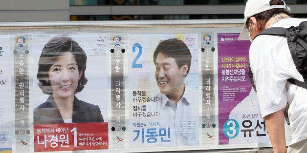 7·30재보궐 선거운동이 시작된 17일 서울 동작구 중앙대 정문 인근에서 한 유권자가 동작을 국회의원 후보자들의 선거벽보를 유심히 살펴보고